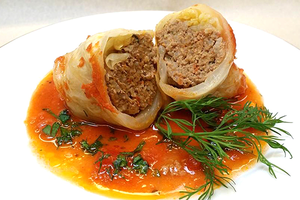 Russian Golubtsi - stuffed cabbage with ground pork, ground beef, rice, fresh herbs and spices in savory tomato sauce.