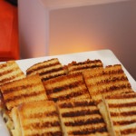 Bite-size grilled cheese sandwiches with gouda and caramelized onion.