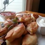 Caramelized onion and potato stuffed piroshki with sour cream and Adjika sauce.