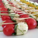 Caprese skewers: imported marinated Buffalo mozzarella, tear drop tomatoes and fresh basil, drizzled with olive oil.