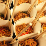 Sesame noodle salad with asian vegetables served in chinese take-out containers with chop sticks and forks.