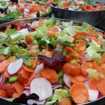 Green salad with carrots, radishes, edamame beans and tomatoes in sesame soy vinaigrette.