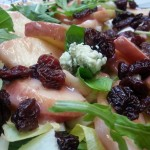 Mixed greens salad with peaches, dried cherries and blue cheese in white balsamic vinaigrette.