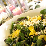 Field greens salad with fresh mango, toasted macadamia nuts, goat cheese in citrus vinaigrette. Accompanied a menu for a tropical-themed wedding.