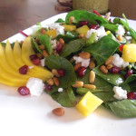 Spinach salad with mango, pomegranate seeds, toasted pine nuts and goat cheese in pomegranate dijon vinaigrette.