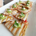 Quesadillas filled with cheese, roasted peppers and mushrooms and topped with guacamole and sour cream.