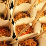 Sesame noodle salad with asian vegetables served in Chinese takeout containers with chop sticks and forks.