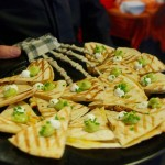 Smoked Chicken Quesadillas topped with guacamole and sour cream.